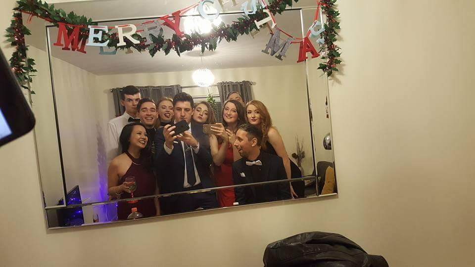 "A group pose in front of a mirror to take a selfie. There is tinsel draped artfully over the top of the mirror as well as a cute felt banner that reads ""Merry Christmas"""